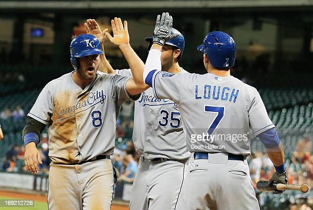 Mike Moustakas of the Kansas City Royals celebrates with Eric Hosmer and David Lough after Moustakas scored a run in the eighth inning against the...