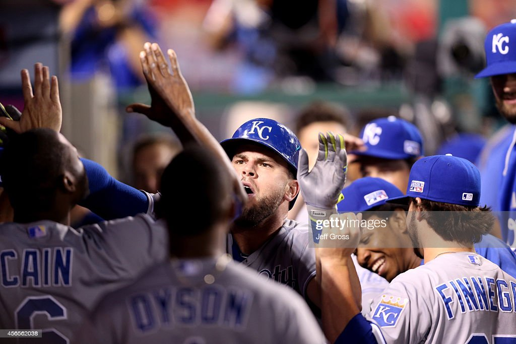 Mike Moustakas #8 of the Kansas City Royals celebrates with his teammates in the dugout after hitting a solo home run in the eleventh inning against the Los Angeles Angels during Game One of the American League Division Series at Angel Stadium of Anaheim on October 2, 2014 in Anaheim, California.