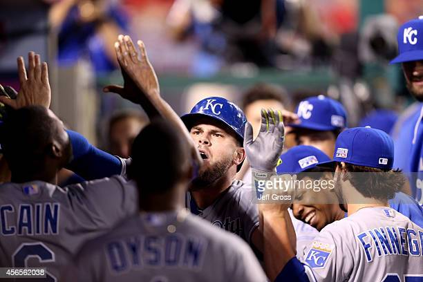 Mike Moustakas of the Kansas City Royals celebrates with his teammates in the dugout after hitting a solo home run in the eleventh inning against the...