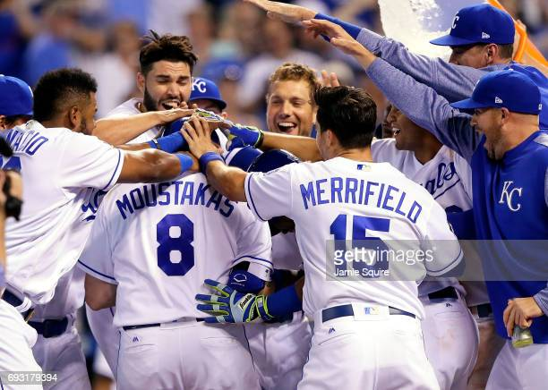 Mike Moustakas of the Kansas City Royals is congratulated by teammates at home plate after hitting a walkoff gamewinning home run during the 9th...
