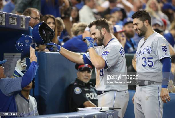 Mike Moustakas of the Kansas City Royals is congratulated by manager Ned Yost and Eric Hosmer after hitting a solo home run in the sixth inning...