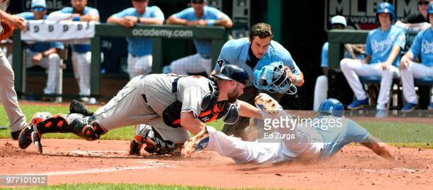 Mike Moustakas of the Kansas City Royals is tagged out by Brian McCann of the Houston Astros as home plate umpire John Tumpane waits to make the call...