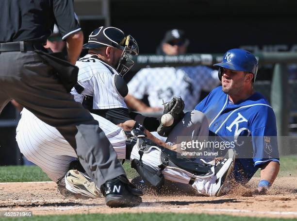 Mike Moustakas of the Kansas City Royals scores the winning run in the top of the 9th inning as Tyler Flowers of the Chicago White Sox drops the ball...