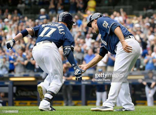 Mike Moustakas of the Milwaukee Brewers celebrates with Ed Sedar of the Milwaukee Brewers after hitting a solo home run in the third inning against...