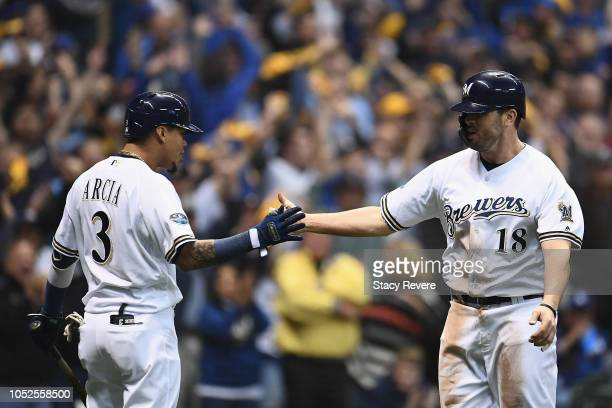 Mike Moustakas of the Milwaukee Brewers celebrates with his teammate Orlando Arcia after scoring a run off of a single hit by Erik Kratz against...
