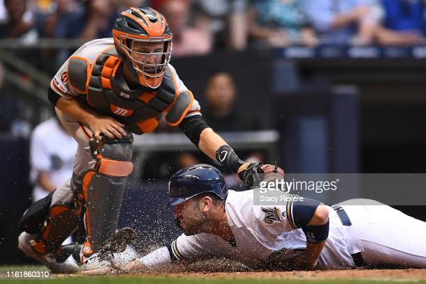 Mike Moustakas of the Milwaukee Brewers is tagged out at home plate by Buster Posey of the San Francisco Giants during the fourth inning at Miller...