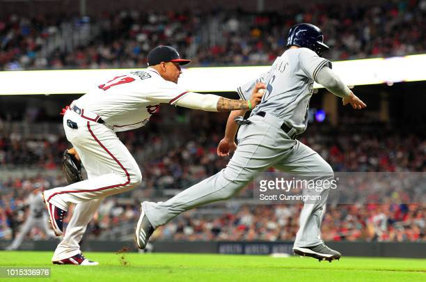 Mike Moustakas of the Milwaukee Brewers is tagged out during an eighth inning rundown by Johan Camargo of the Atlanta Braves at SunTrust Park on...