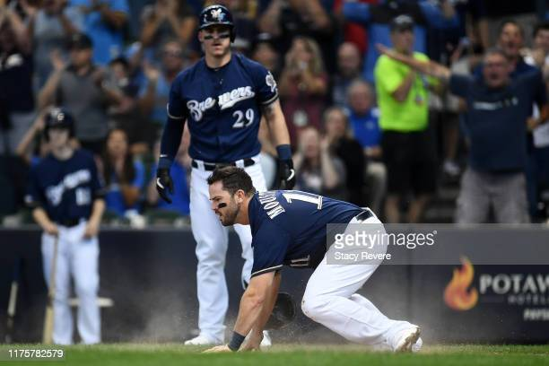 Mike Moustakas of the Milwaukee Brewers scores against the San Diego Padres during the first inning at Miller Park on September 19 2019 in Milwaukee...