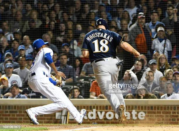 Mike Moustakas of the Milwaukee Brewers scores on a wild pitch as Carl Edwards Jr #6 of the Chicago Cubs tries to tag him during the sixth inning on...