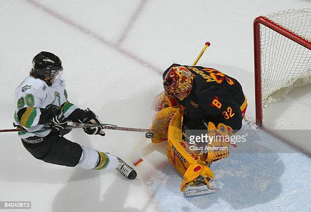 Mike Murphy of the Belleville Bulls makes a stop on Philip McRae of the London Knights in a game on December 12, 2008 at the John Labatt Centre in...