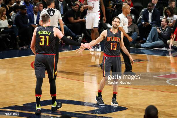 Mike Muscala and Jose Calderon of the Atlanta Hawks high five each other during the game against the Washington Wizards during Game Two of the...