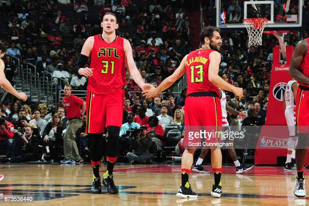 Mike Muscala and Jose Calderon of the Atlanta Hawks high five each other during the game against the Washington Wizards in Game Five of the Eastern...