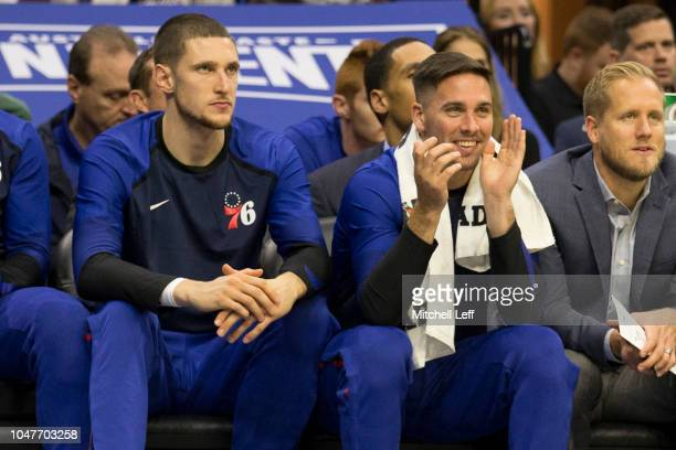 Mike Muscala and TJ McConnell of the Philadelphia 76ers react from the bench against Melbourne United in the preseason game at Wells Fargo Center on...