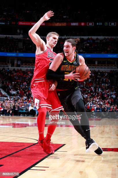 Mike Muscala of the Atlanta Hawks handles the ball against Lauri Markkanen of the Chicago Bulls on October 26 2017 at the United Center in Chicago...