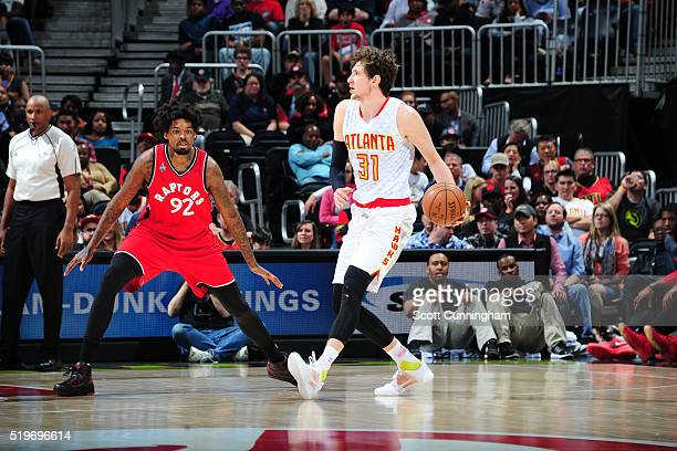 Mike Muscala of the Atlanta Hawks handles the ball against Lucas Nogueira of the Toronto Raptors on April 7 2016 at Philips Arena in Atlanta Georgia...