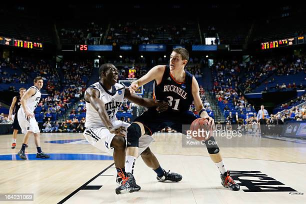 Mike Muscala of the Bucknell Bison drives against Khyle Marshall of the Butler Bulldogs in the first half during the second round of the 2013 NCAA...