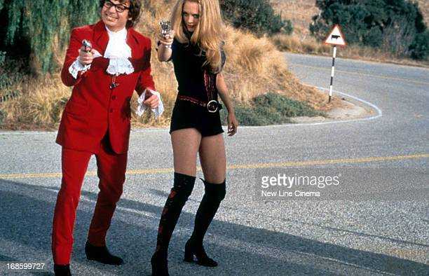 Mike Myers and Heather Graham standing on a winding road with pointed guns in their hands in a scene from the film 'Austin Powers The Spy Who Shagged...
