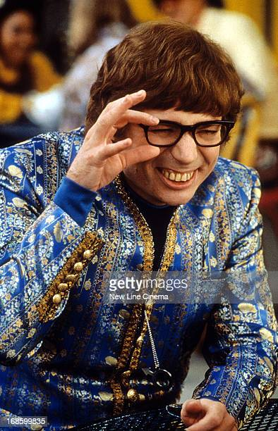 Mike Myers wearing an ornate blue jacket while squinting through his black rimmed glasses in a scene from the film 'Austin Powers The Spy Who Shagged...