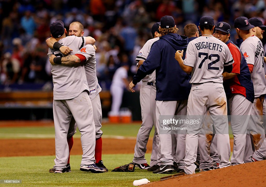 Mike Napoli #12 and Jonny Gomes #5 of the Boston Red Sox celebrate with teammates after defeating the Tampa Bay Rays 3-1 in Game Four of the American League Division Series at Tropicana Field on October 8, 2013 in St Petersburg, Florida.