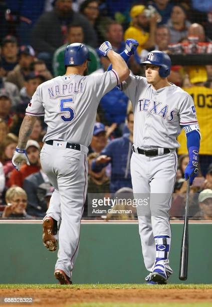Mike Napoli high fives Ryan Rua of the Teaxs Rangers after hitting a solo home run in the fifth inning of a game against the Boston Red Sox at Fenway...