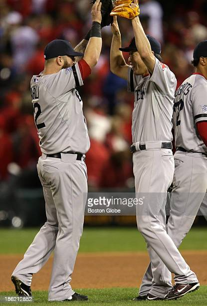 Mike Napoli left and Koji Uehara of the Red Sox celebrate after they picked the Cardinal Kolten Wong off first base to end the game The St Louis...