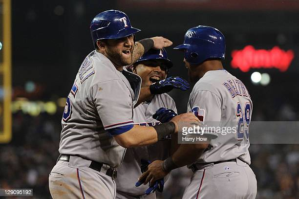 Mike Napoli, Nelson Cruz and Adrian Beltre of the Texas Rangers celebrate after Cruz's three run home run in the 11th inning of Game Four of the...
