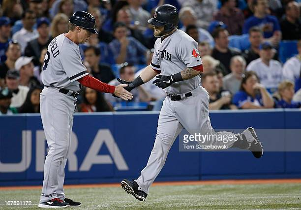 Mike Napoli of the Boston Red Sox is congratulated by third base coach Brian Butterfield after hitting a solo home run in the fourth inning during...