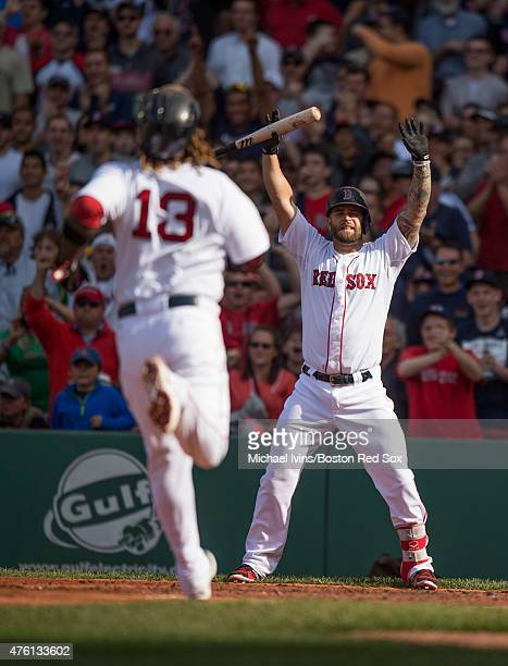 Mike Napoli of the Boston Red Sox signals to Hanley Ramirez as he rounds third base during the third inning against the Oakland Athletics at Fenway...