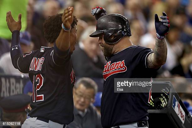Mike Napoli of the Cleveland Indians celebrates with teammate Francisco Lindor after hitting a solo home run in the fourth inning against Marcus...