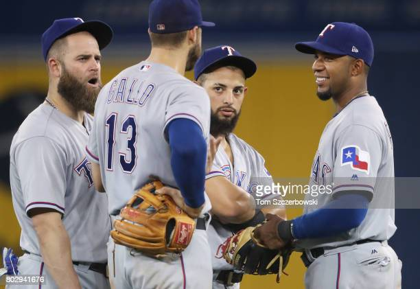 Mike Napoli of the Texas Rangers and Joey Gallo and Rougned Odor and Elvis Andrus gather in the infield and talk during a break in the action during...