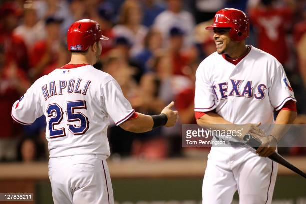 Mike Napoli of the Texas Rangers and Nelson Cruz celebrate scoring on a tworun RBI double by Ian Kinsler in the sixth inning of Game Two of the...
