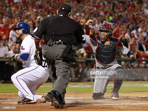 Mike Napoli of the Texas Rangers is called out at home plate by umpire Alfonso Marquez after the tag by Yadier Molina of the St Louis Cardinals in...
