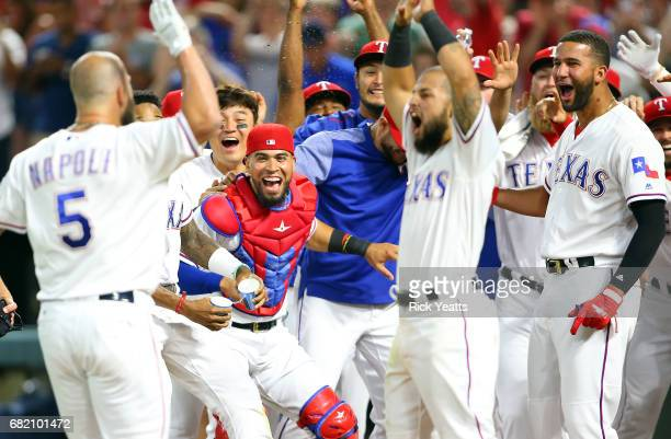 Mike Napoli of the Texas Rangers is congratulated by his teammates for hitting a three run walk off home run in the ninth inning against the San...