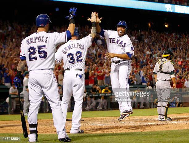 Mike Napoli of the Texas Rangers looks on as Josh Hamilton Michael Young and Nelson Cruz score on a threerun triple by Craig Gentry in the eighth...