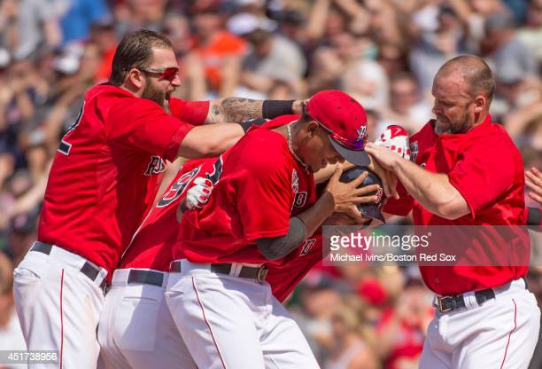 Mike Napoli Xander Bogaerts and David Ross of the Boston Red Sox mob Jonathan Herrera after he hit a walk off single against the Baltimore Orioles in...