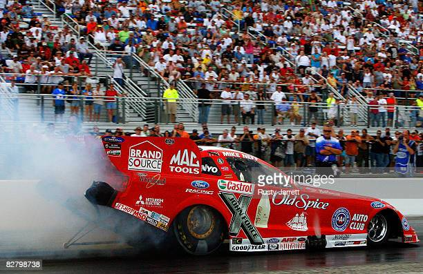 Mike Neff driver of the Old Spice funny car does his burn out during qualifying for the NHRA Carolinas Nationals at the Zmax Dragway on September 12...