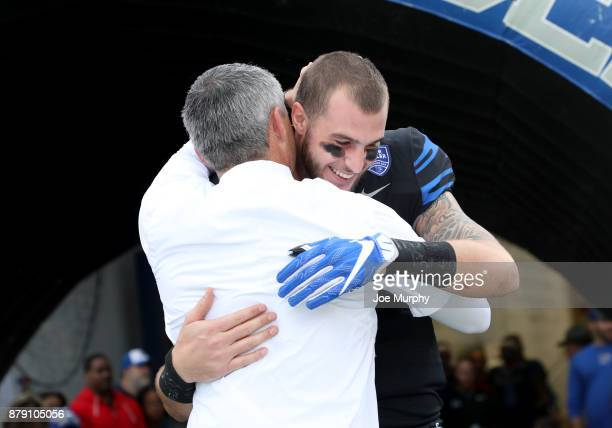 Mike Norvell head coach of the Memphis Tigers hugs Riley Ferguson of the Memphis Tigers during Senior Day festivities before the game against the...