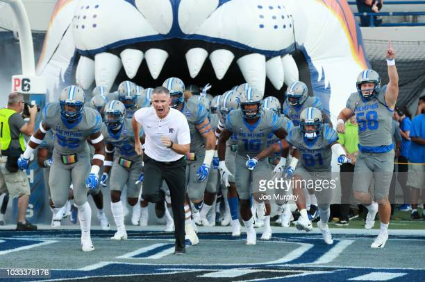 Mike Norvell, head coach of the Memphis Tigers leads his team on to the field against the Georgia State Panthers on September 14, 2018 at Liberty...