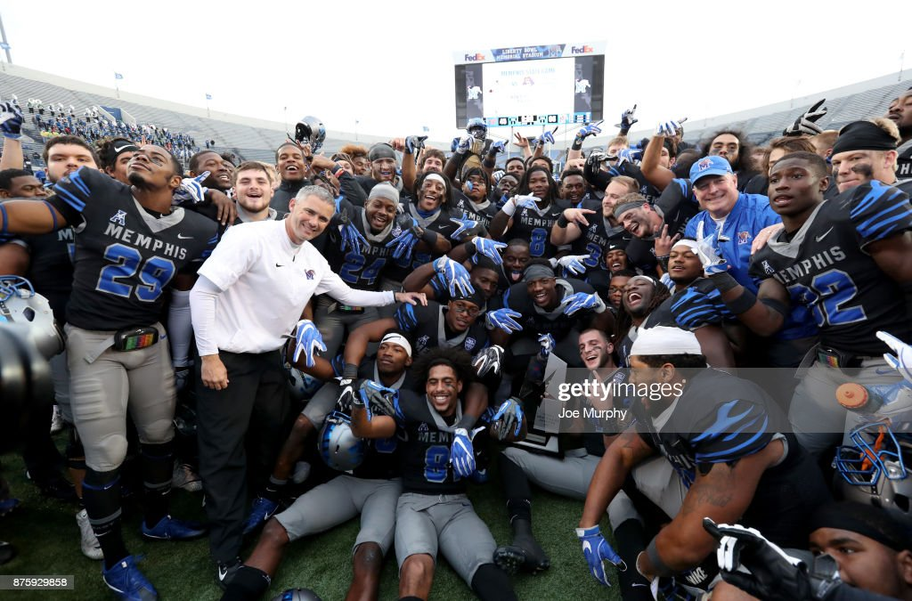 Mike Norvell, head coach of the Memphis Tigers poses with his team after winning the West Division of the AAC after defeating the SMU Mustangs on November 18, 2017 at Liberty Bowl Memorial Stadium in Memphis, Tennessee. Memphis defeated SMU