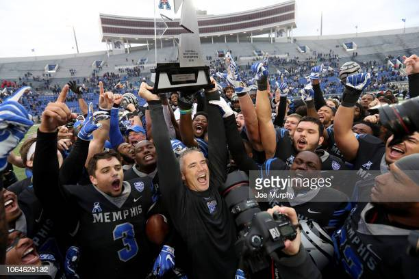 Mike Norvell, head coach of the Memphis Tigers raises the AAC West Division trophy with his players against the Houston Cougars during the second...