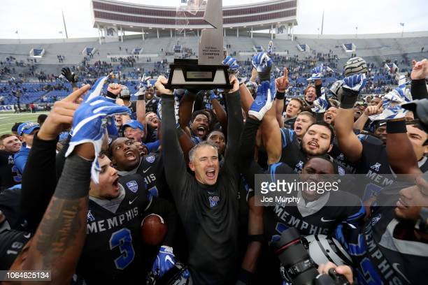 Mike Norvell head coach of the Memphis Tigers raises the AAC West Division trophy with his players against the Houston Cougars during the second half...