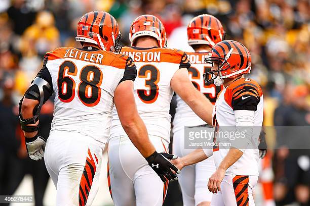 Mike Nugent of the Cincinnati Bengals shakes hands with teammate Kevin Zeitler after hitting a 44 yard field goal in the 4th quarter of the game at...