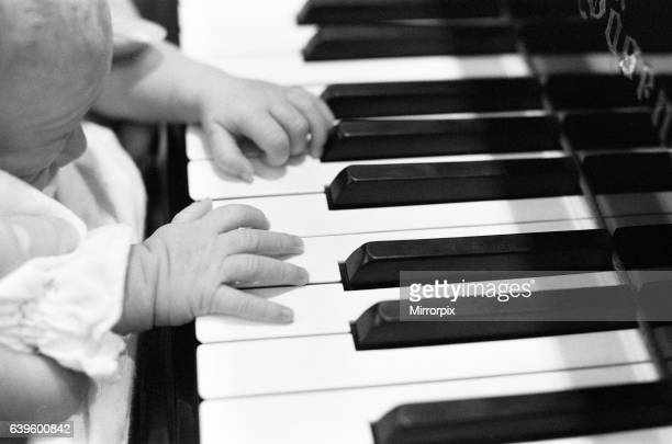 Mike Oldfield musician and composer pictured at home with family baby son Dougal not too young to start learning the keyboard Buckinghamshire...