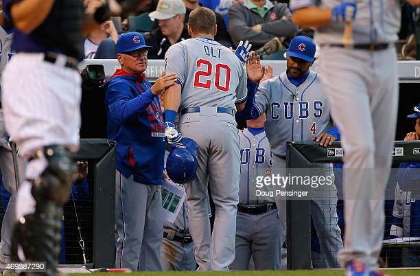 Mike Olt of the Chicago Cubs is welcomed to the dugout by manager Joe Maddon of the Chicago Cubs and Dave Martinez of the Chicago Cubs after his solo...