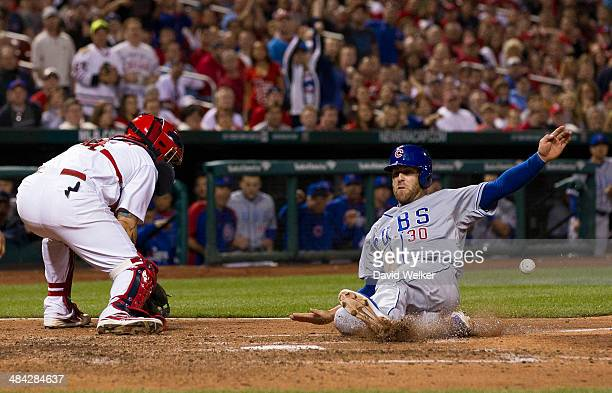 Mike Olt of the Chicago Cubs slides into home plate to score in the eighth inning during a game against the St Louis Cardinals at Busch Stadium on...