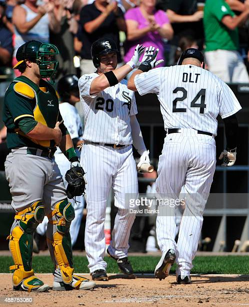 Mike Olt of the Chicago White Sox is greeted by JB Shuck after hitting a home run against the Oakland Athletics during the fourth inning on September...