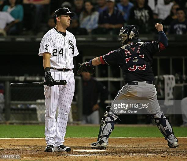 Mike Olt of the Chicago White Sox reacts after stirking out in the 9th inning as Roberto Perez of the Cleveland Indians throws the ball back to the...