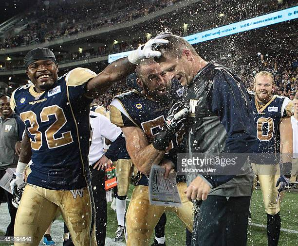 Mike O'Shea, head coach of the Winnipeg Blue Bombers, gets congratulated by Nic Grigsby after he had a drink poured on top of him at the end of...