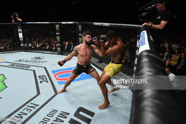 Mike Perry punches Alex Oliveira of Brazil in their welterweight bout during the UFC Fight Night event at BBT Center on April 27 2019 in Sunrise...