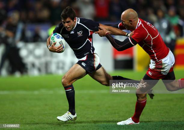 Mike Petri of USA hands off Igor Klyuchnikov of Russia to score the opening try during the IRB 2011 Rugby World Cup Pool C match between Russia and...